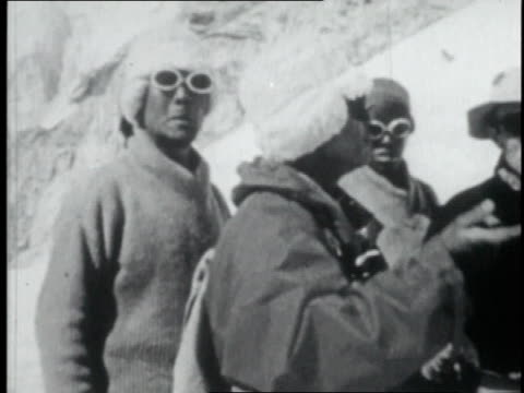 vidéos et rushes de ws mountaineer talking to other mountaineers wearing snow goggles on mount everest's lower slopes / nepal - 1952