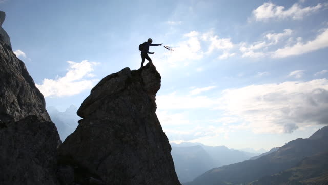 Mountaineer throws rope from rock pinnacle in high mountains
