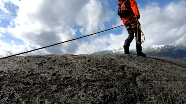 mountaineer traverses granite ridge crest, with climbing rope - rope stock videos & royalty-free footage