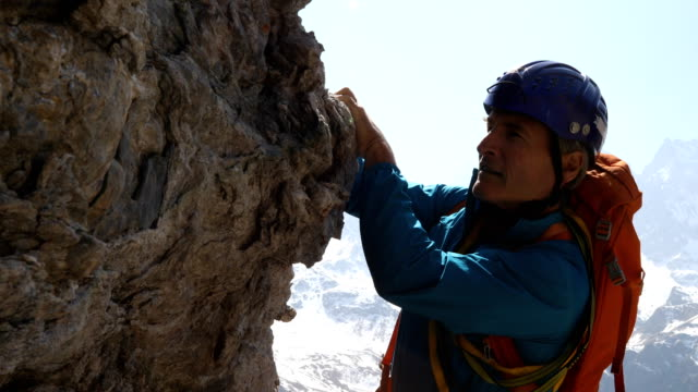 mountaineer traverses near summit of high mountain pinnacle with dramatic alpine view behind - corda video stock e b–roll