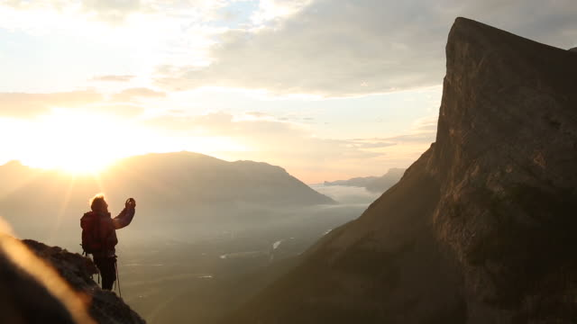 Mountaineer traverses to cliff edge, sun rises behind