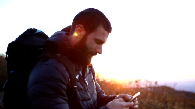 mountaineer typing a message while resting on sunset - close up - beard stock videos & royalty-free footage