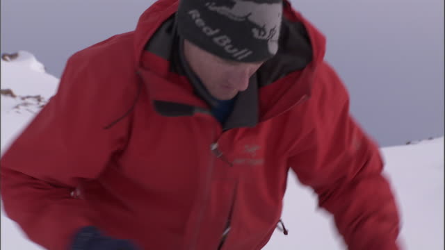 a mountaineer uses a shovel to dig in the snow. - überleben stock-videos und b-roll-filmmaterial