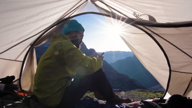 vídeos de stock e filmes b-roll de mountaineer wakes up in tent at sunrise - chapéu