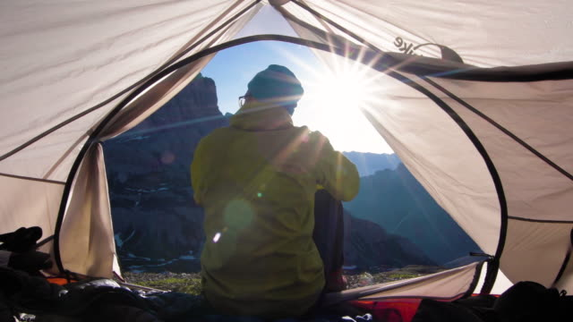 mountaineer wakes up in tent at sunrise - tent stock videos & royalty-free footage