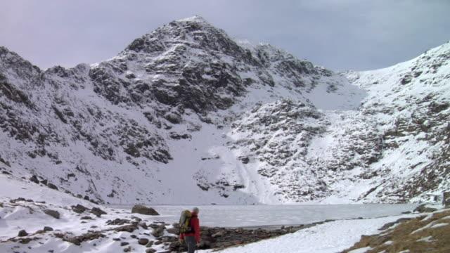 ws mountaineer walking by frozen mountain lake, snow covered mountain in background / llanberis, snowdonia, uk - snowdonia stock videos & royalty-free footage