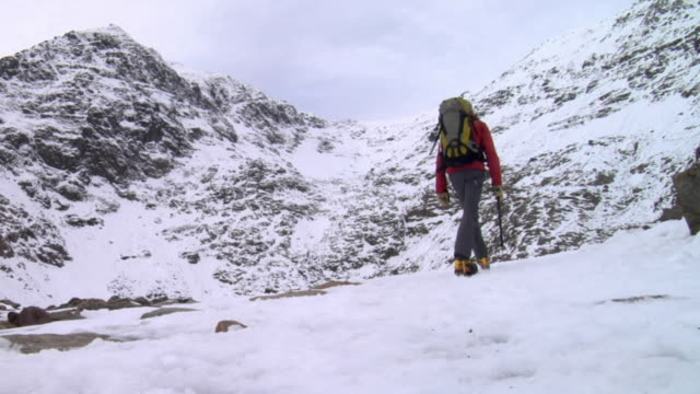 ws mountaineer walking on snow towards mountain / llanberis, snowdonia, uk - snowdonia video stock e b–roll