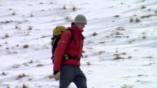 ms ts pan mountaineer walking through snow slope / llanberis, snowdonia, uk - snowdonia video stock e b–roll