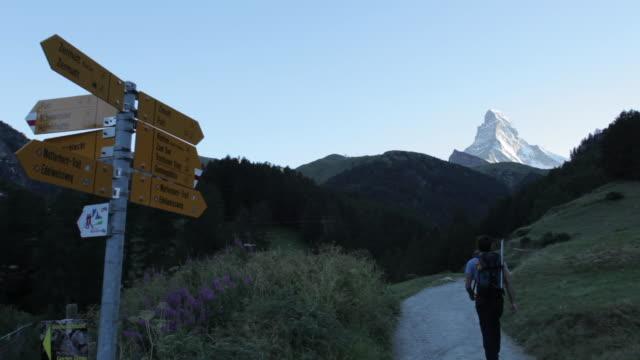 Mountaineer walking towards Matterhorn in European Alps.