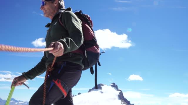 mountaineer walks along cornice - schneeverwehung stock-videos und b-roll-filmmaterial