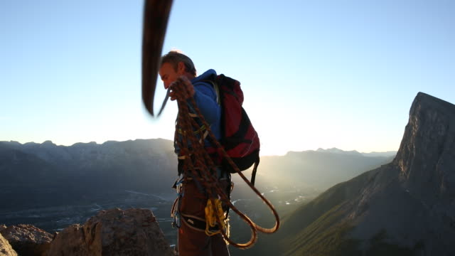 Mountaineer walks to edge of rock cliff, look out to sunrise