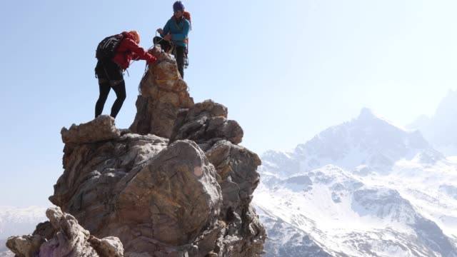 mountaineering couple approach pinnacle summit - distant stock videos and b-roll footage