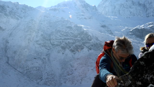 Mountaineering couple ascend ledge to pinnacle summit