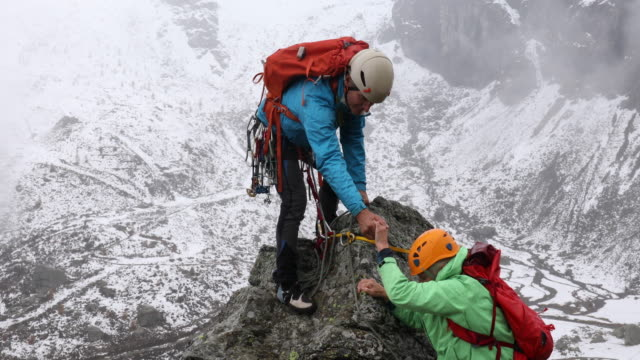 mountaineering couple ascend summit during storm - sports helmet stock videos and b-roll footage