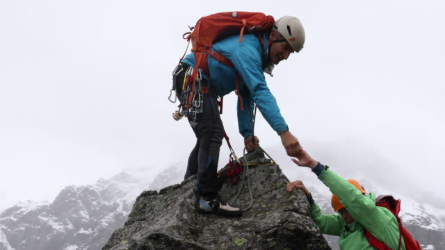 mountaineering couple ascend summit during storm - sfida video stock e b–roll