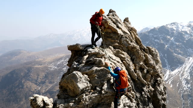 mountaineering couple climb steep rock pinnacle - mountain stock videos & royalty-free footage