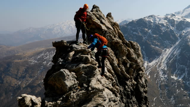 Mountaineering couple climb steep rock pinnacle