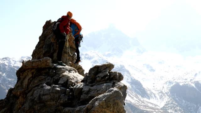 mountaineering couple climb steep rock pinnacle - snowcapped mountain stock videos & royalty-free footage