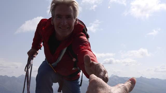 vidéos et rushes de un couple d'alpinistes atteint le sommet de la montagne - corde