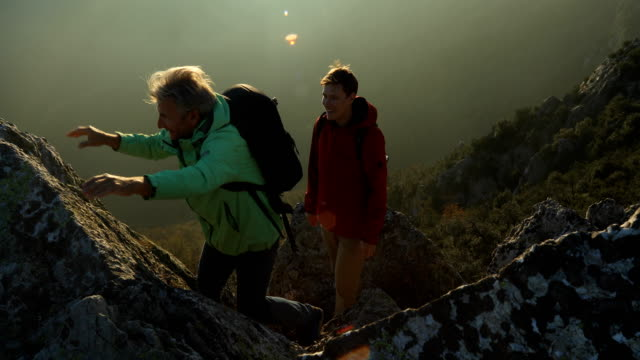 mountaineering father and son make their way up rocky ravine - geographical locations stock videos & royalty-free footage