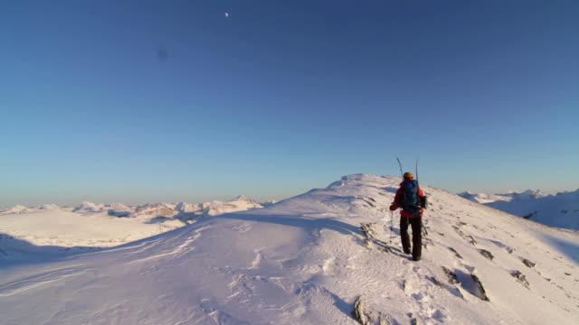 mountaineers ascend high snow capped mountain - bastoncino da sci video stock e b–roll