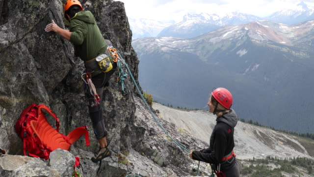 mountaineers ascend rock cliff, above mountains - safety harness stock videos & royalty-free footage