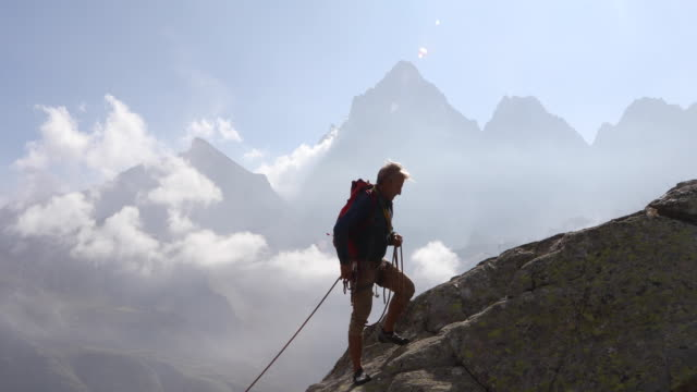 mountaineers ascend rock ridge, above valley - rope stock videos & royalty-free footage