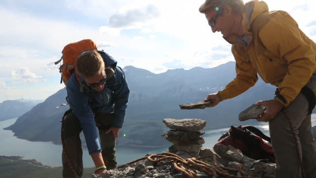 mountaineers build rock cairn on mtn summit together - stacking stock videos & royalty-free footage