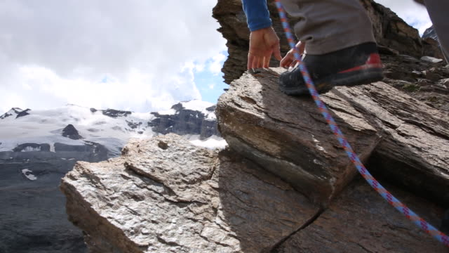 mountaineers climb rock step at base of matterhorn - rope stock videos & royalty-free footage