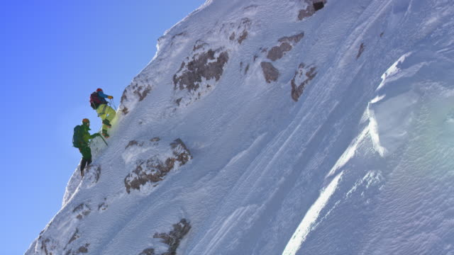 PAN Mountaineers climbing a snowy steep slope in winter