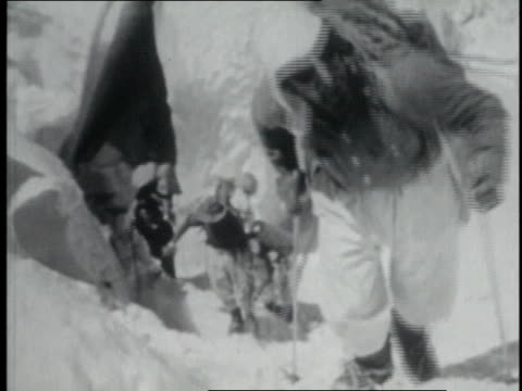 stockvideo's en b-roll-footage met mountaineers climbing up steep mountainside / line of mountaineers across plain on lower slopes of mountain / two men talking while one smokes a... - tenzing norgay