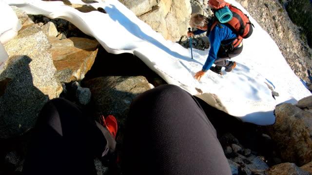 vídeos de stock, filmes e b-roll de montanhistas descem da cimeira através da tundra alpina elevada - snow cornice