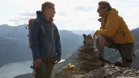 mountaineers have conversation by rock cairn on mtn summit - leisure activity stock videos & royalty-free footage
