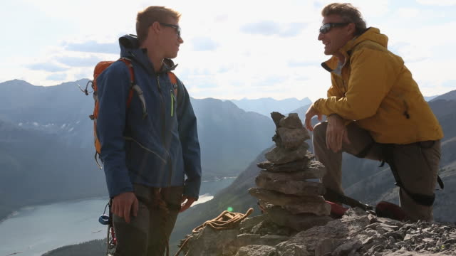 mountaineers have conversation by rock cairn on mtn summit - recreational pursuit stock videos & royalty-free footage