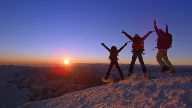 SLO MO Mountaineers jumping on snowy mountain top at sunset
