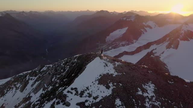 Mountaineers on a summit during sunrise
