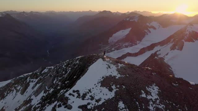 mountaineers on a summit during sunrise - kreuz religiöser gegenstand stock-videos und b-roll-filmmaterial