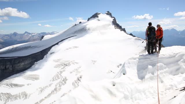 Mountaineers pause on skyline ridge, look to glaciated mountains