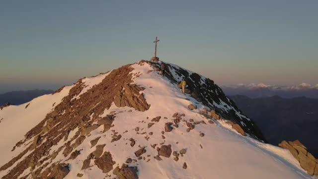 Mountaineers reaching a summit during sunrise