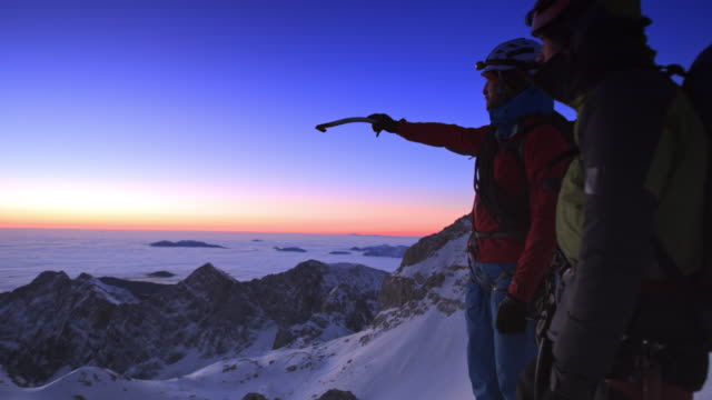 PAN Mountaineers standing on the snowy mountain top at dusk