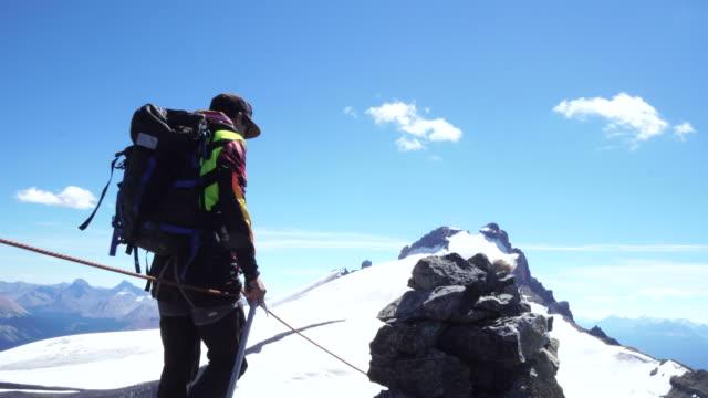 vídeos y material grabado en eventos de stock de mountaineers traverse ridge above glaciated mountains - abrigo de invierno