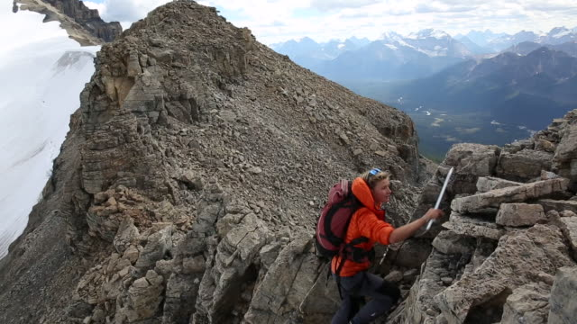 Mountaineers traverse skyline ridge, above glaciated mountains