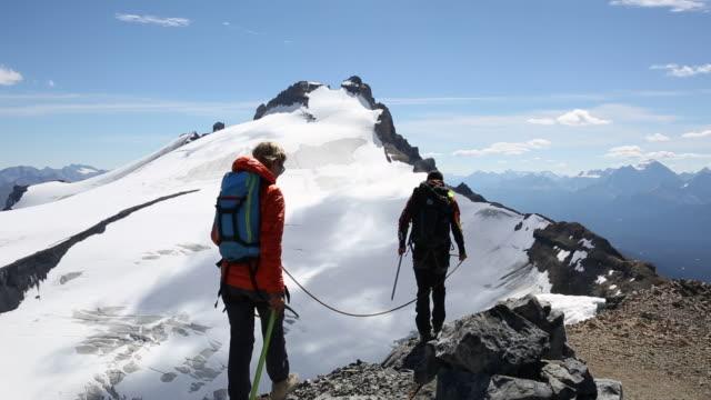 mountaineers traverse skyline ridge, look to glaciated mountains - wintermantel stock-videos und b-roll-filmmaterial