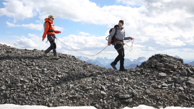 Mountaineers traverse skyline ridge, look to glaciated mountains