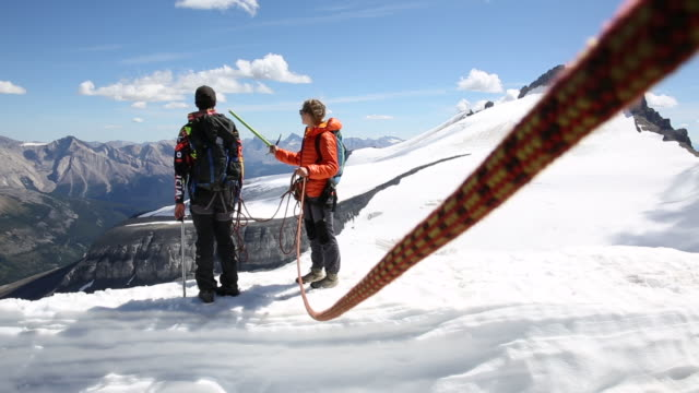 Mountaineers traverse snow ridge, look to glaciated mountains