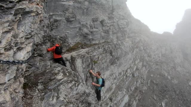 vidéos et rushes de les alpinistes traversent la falaise verticale, utilisant l'ancre de chaîne - escalade