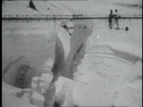 vidéos et rushes de montage mountaineers using rope pulley system to cross a crevasse on mount everest's lower slopes / nepal - 1952