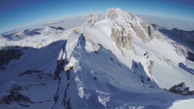 POV Mountaineers walking across a snowy narrow ridge