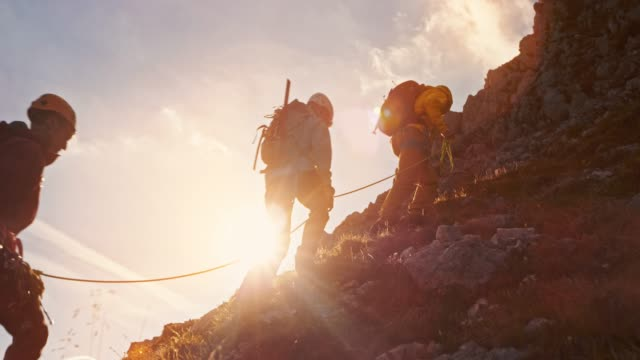 td mountaineers walking slowly towards the mountain top at sunset - climbing rope stock videos & royalty-free footage