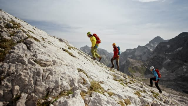 mountaineers walking up a rocky slope in sunshine - climbing stock videos & royalty-free footage